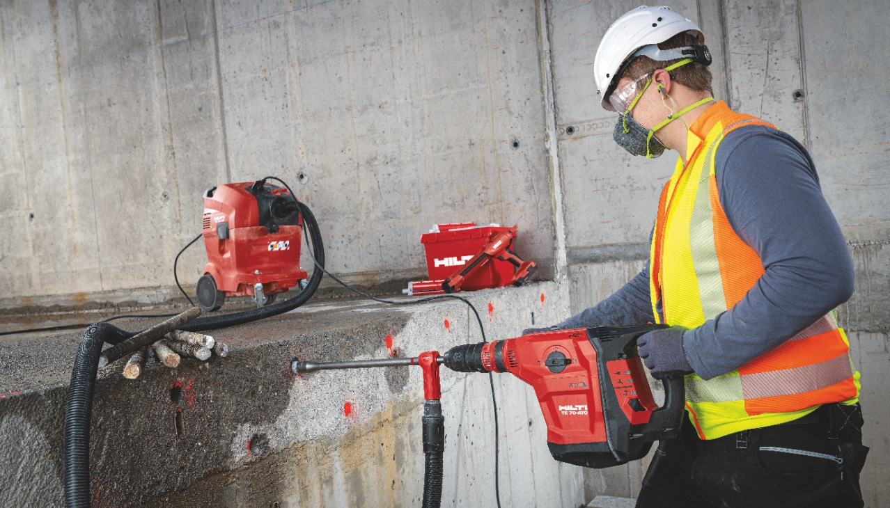 Construction worker on a building site using a Hilti rotary hammer connected to a vacuum to dustlessly drill holes in concrete.